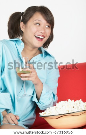 Asian woman wearing man's shirt on sofa with wine