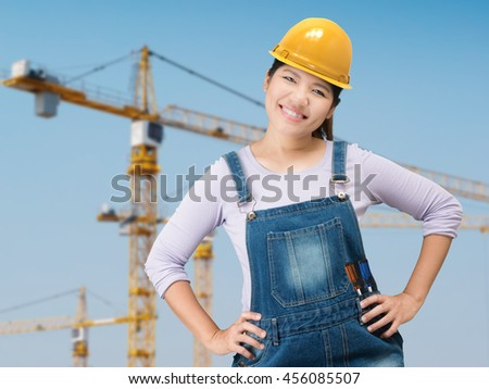 asian woman wearing yellow safety helmet with construction site background