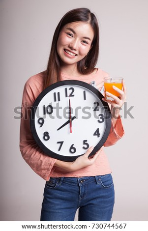 Asian woman with a clock drink orange juice on gray background