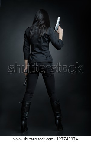 Asian woman with a pistol - stock photo