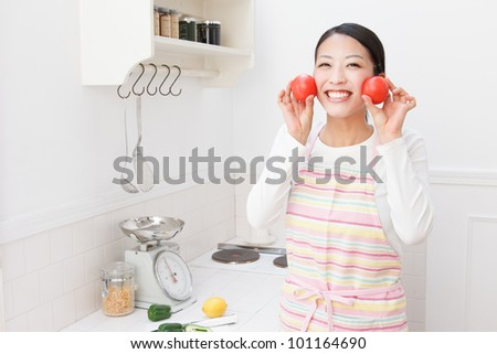 Asian woman with a tomato in the kitchen - stock photo
