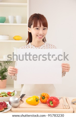 Asian woman with an empty board in the kitchen - stock photo