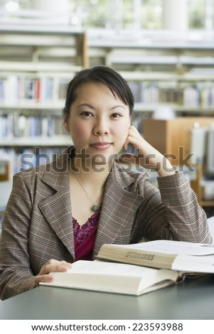 Asian woman with books in library