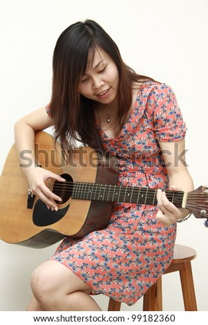 Asian woman with guitar in studio - stock photo
