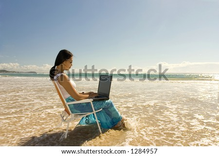 Asian woman with laptop working at the beach