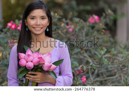 Asian woman with lotus flowers bud posing in front of a desert rose tree - stock photo
