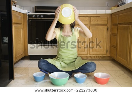 Asian woman with mixing bowls on floor - stock photo