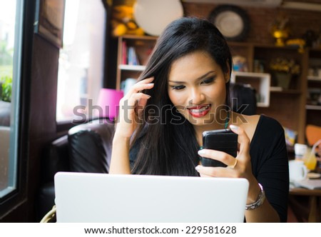 Asian  woman with mobile phone  and laptop - stock photo