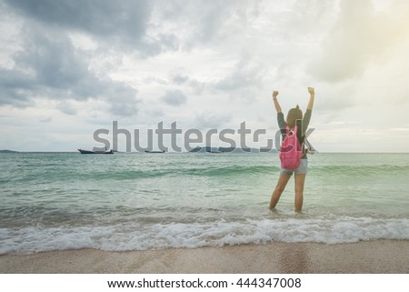 Asian woman with pink backpack and camera stand and stretching her arms into the sky enjoy and happy at sea