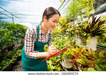 Asian woman writing down names of plants in the greenhouse - stock photo