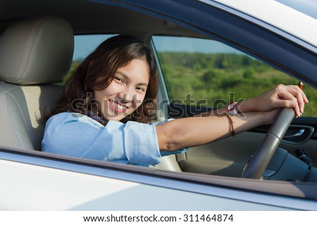 Asian woman, Young female driving happy about her new car or drivers license - stock photo