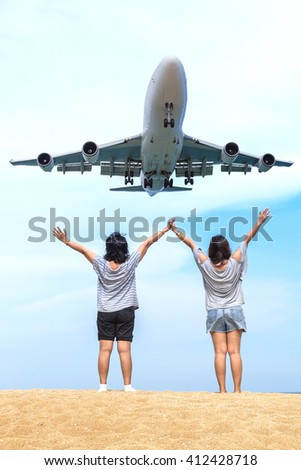 Asian womans raise hands on the beach with airplane landing over head.
