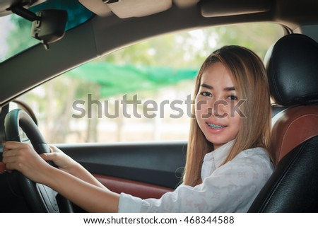 Asian women are driving cars on the road.