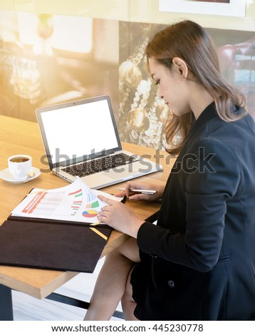 Asian women Businesswoman Analyzing Graph While Laptop On Office Desk. - stock photo