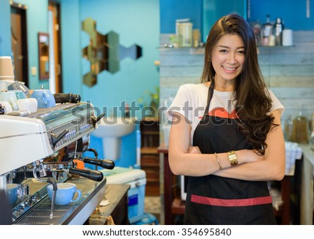 Asian women coffee barista successful small business owner standing with crossed arms  beside coffee machine in counter  - stock photo
