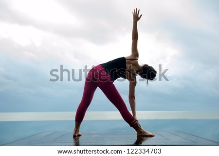 Asian women do Yoga with sea view in cloudy day