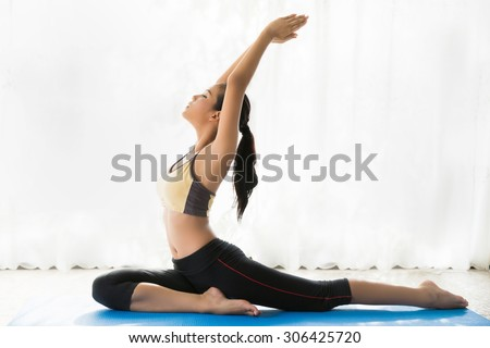 Asian women doing yoga poses. she was in the house - stock photo