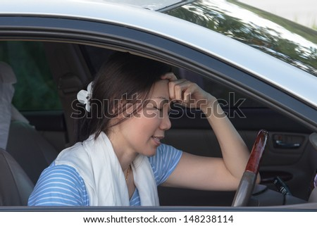 Asian women have a headache in the car.