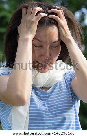 Asian women have a severe headache. - stock photo