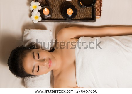 Asian women to sleep, relax, spa and massage in the top corner of the couch with candles. - stock photo