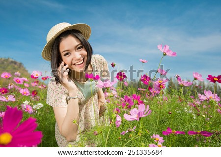 Asian women Use a phone conversation with a friend Cosmos flowers are happy to talk - stock photo