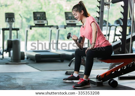 Asian women workout lifting a dumbbell in the gym. - stock photo