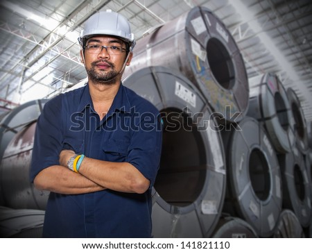 Asian worker at a coil material warehouse - stock photo