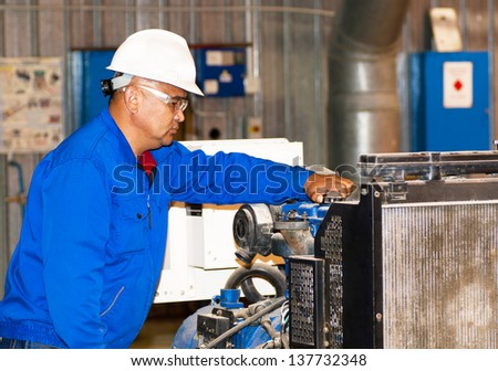 asian worker repairs an industrial equipment