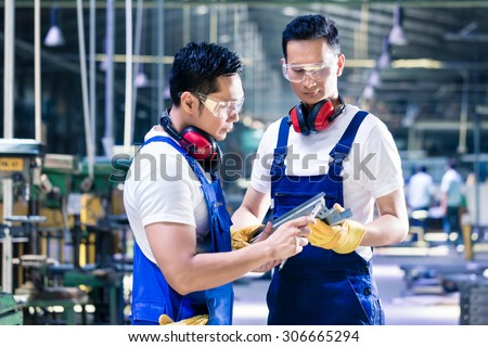 Asian worker team checking work piece in production plant discussing the measurements - stock photo