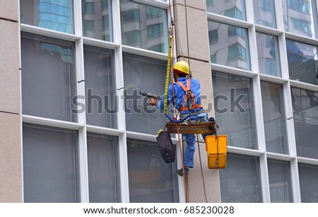 Asian worker washing the high building