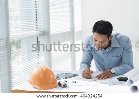 Asian young architect working on blueprint in the office - stock photo