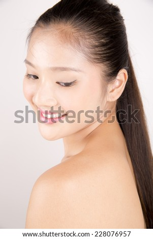 Asian young beautiful woman with flawless complexion smiling and looking down