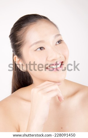 Asian young beautiful woman with flawless complexion smiling and touching face close up