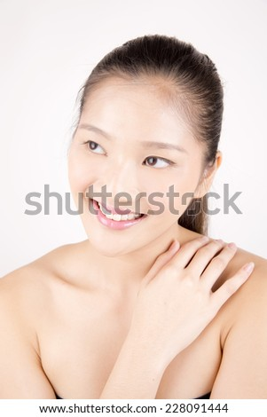 Asian young beautiful woman with flawless complexion smiling and touching shoulder