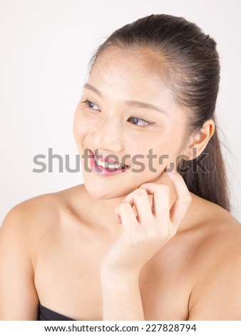 Asian young beautiful woman with flawless complexion touching face smiling