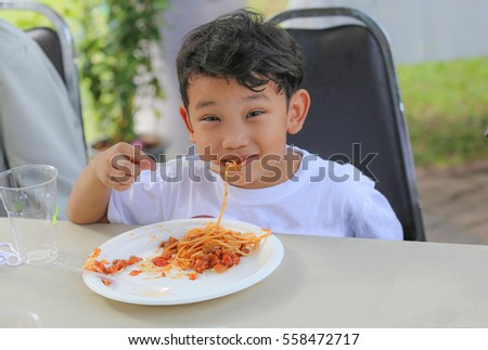 Asian young boy eating tomato sauce spaghetti for his lunch. Feeling enjoy, delicious and happy.