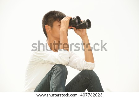 Asian young boy sit is seeking binoculars .