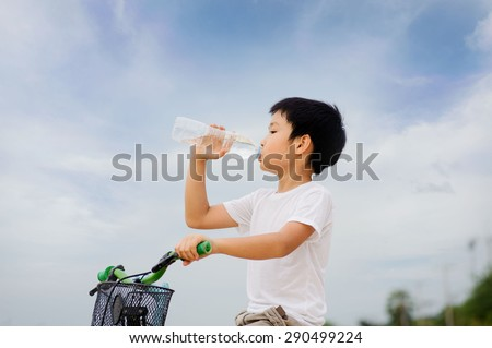 Asian young boy sit on bicycle  drinking fresh water from plastic bottle after sport in daylight - stock photo