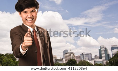 Asian young business man pointing finger at you - stock photo