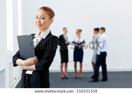 Asian young business woman holding folder with colleagues at background - stock photo