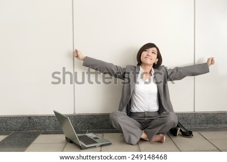 Asian young business woman take off her shoes and relax sitting on ground in modern building. - stock photo