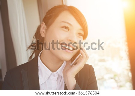 Asian young business woman using cellphone, closeup portrait in hotel.