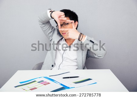 Asian young businessman sitting at the table and making frame with fingers over gray background. Looking at camera through fingers - stock photo