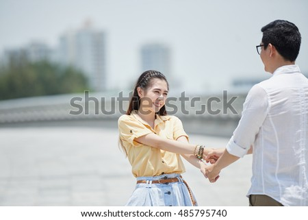 Asian young couple holding hands and dancing outdoors
