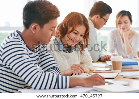 Asian young couple reading students book together