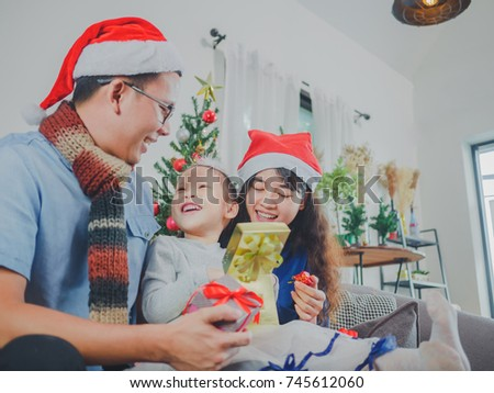 Asian young family on Christmas exchanging presents and enjoying their time together. Focus on the little girl.