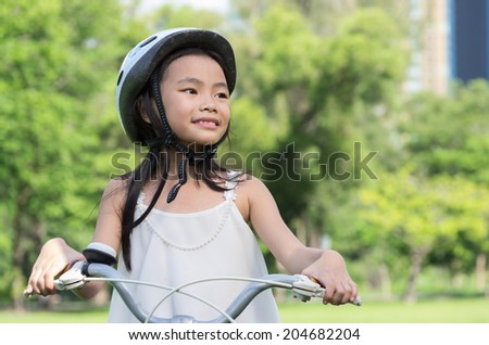 Asian young girl riding the bicycle with natural background. - stock photo