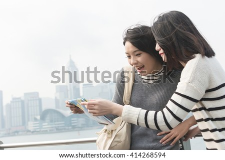 Asian young girl travel and look the map at Victoria Harbor, Hong Kong, Asia - stock photo
