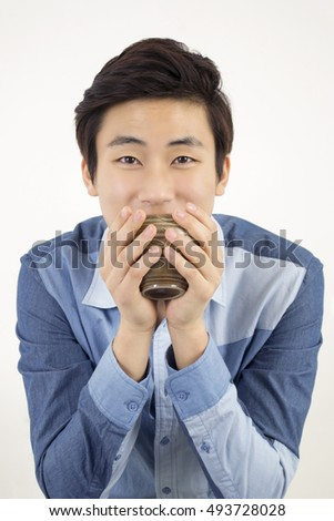 Asian young handsome man holding a ceramic cup of tea