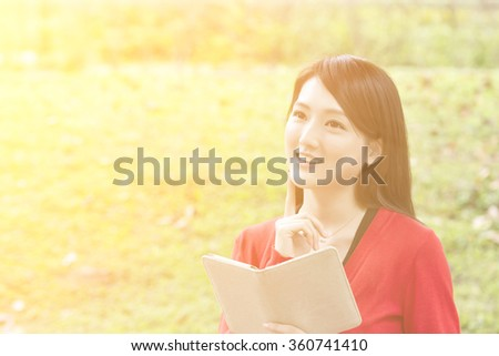 Asian young lady read book at outdoor in city. - stock photo